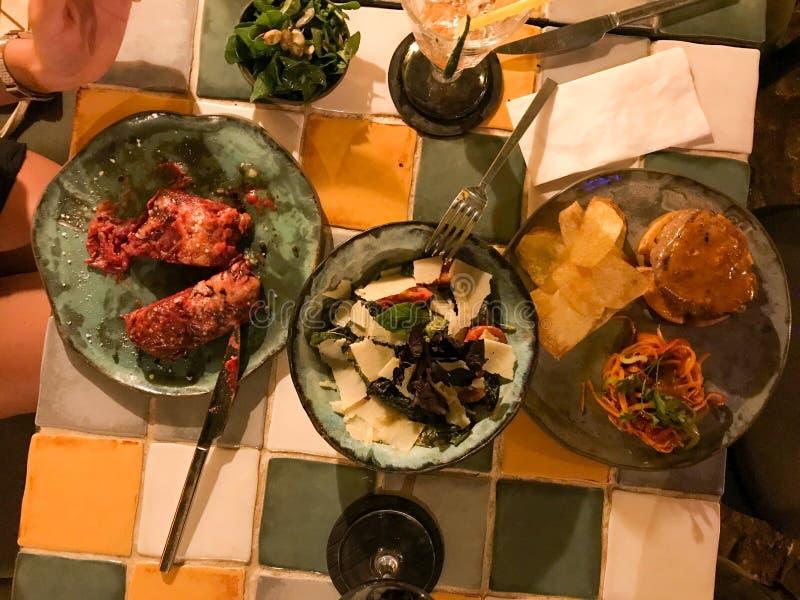 Couplez le Tableau de dîner avec le gratin végétal, la salade de parmesan, le boeuf avec des puces et la salade de carotte au res images stock