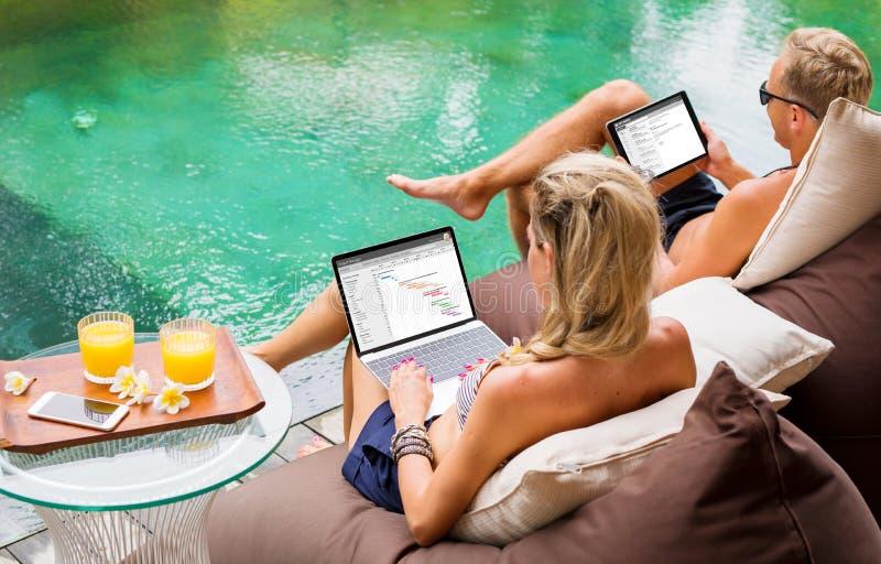 Couplez le travail sur des ordinateurs tout en détendant par la piscine photo stock