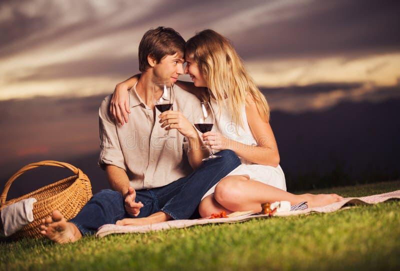 Couplez le verre à boire de vin sur le pique-nique romantique de coucher du soleil images libres de droits