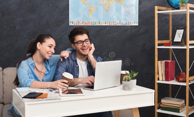 Couplez le voyage de planification, passant en revue sur l'ordinateur portable à la maison photos stock