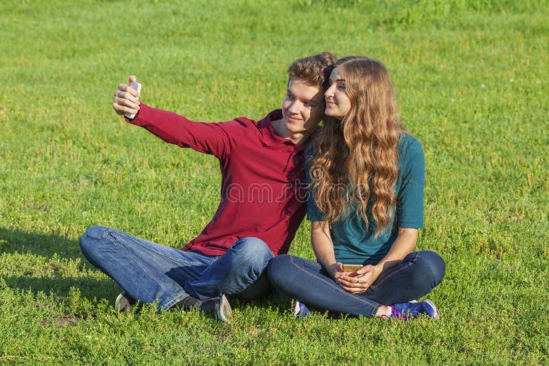 Couplez les adolescents s'asseyant sur la pelouse verte avec un smartphone photos stock