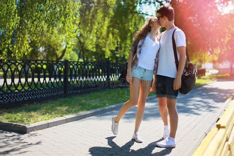 Couplez les ados dans l'amour marchant en parc dans le jour d'été, jeunesse images libres de droits