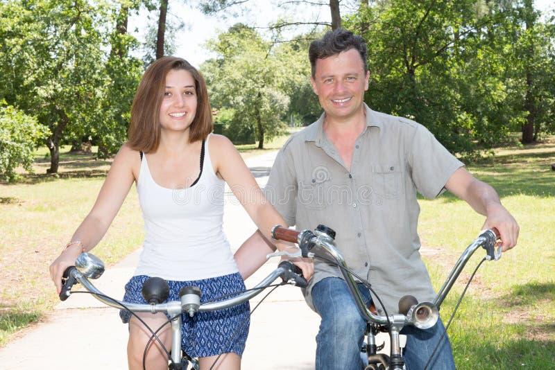 Couplez les bicyclettes d'équitation dehors dans le concept sain de vacances d'amusement de mode de vie image libre de droits