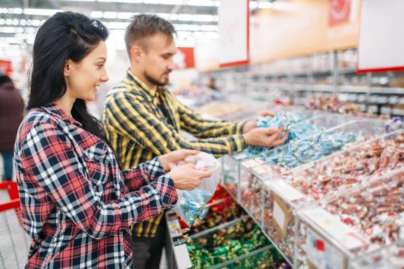 Couplez les bonbons et les sucreries de achat dans le supermarché photos stock
