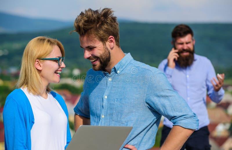 Couplez les collègues flirtant tandis que patron occupé avec la conversation mobile Avantages mobiles d'Internet Couples ayant l' photo libre de droits