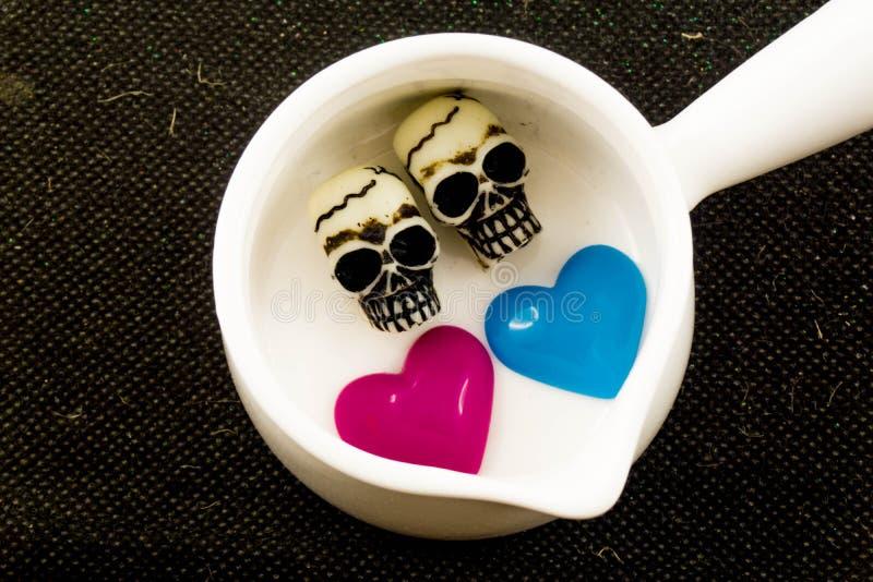 Couplez les crânes avec les coeurs roses et bleus dans le pot blanc image libre de droits