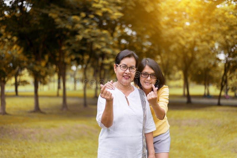 Couplez les mains asiatiques de femme montrant le mini coeur et détendez au parc public pendant le matin ensemble, heureux et en  photo libre de droits