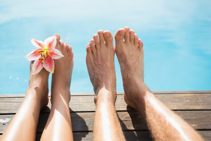 Couplez les pieds contre la piscine un jour ensoleillé photo stock