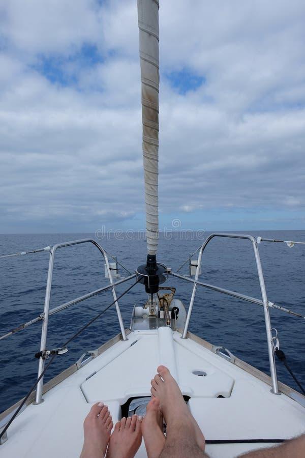 Couplez les pieds sur le voilier avec la vue de mer images libres de droits