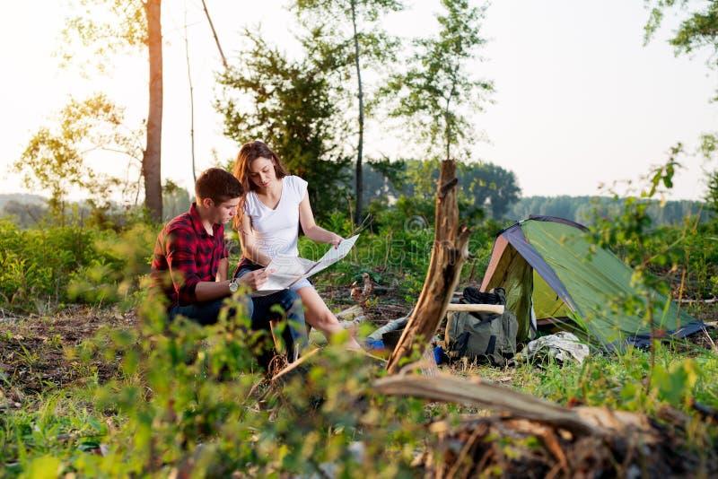 Couplez les randonneurs dans les montagnes, ils regarde la carte images stock