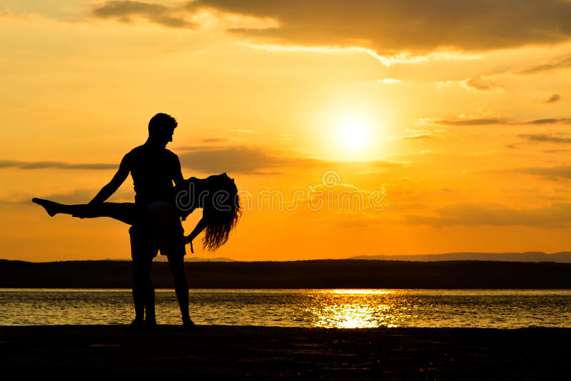 Couplez les silhouettes se tenant au coucher du soleil par la mer, dansant photographie stock libre de droits