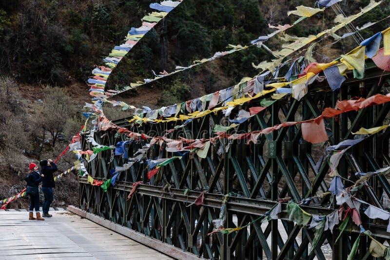 Couplez les touristes avec les drapeaux tibétains colorés de prière de larme ondulant et enveloppés avec le pont au-dessus de la  photos libres de droits