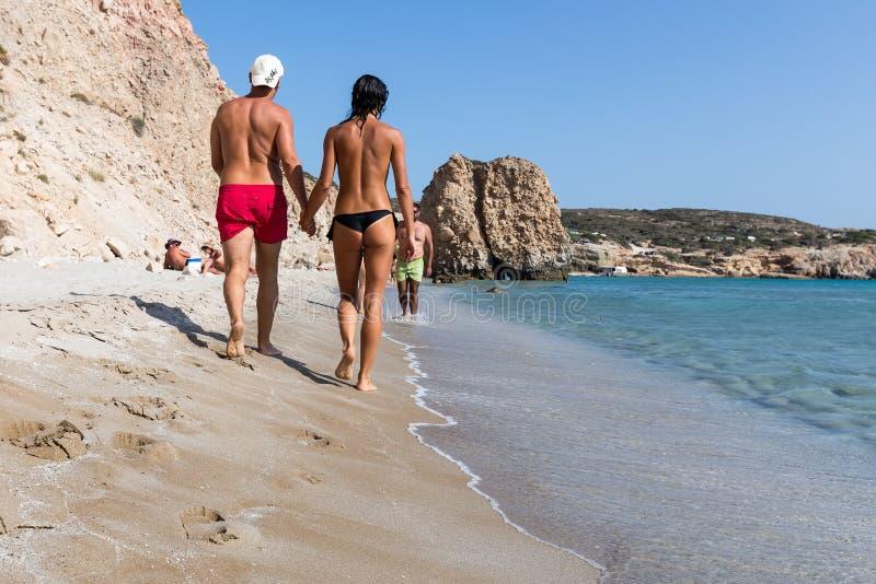 Couplez les touristes marchant près de l'eau claire du beau fi photographie stock
