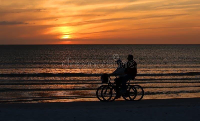 Couplez les vélos d'équitation sur la plage au coucher du soleil images stock