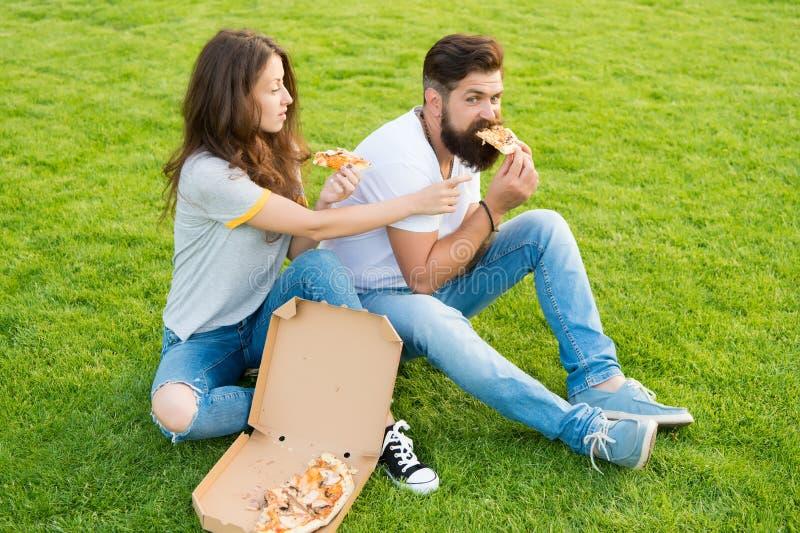 Couplez manger de la pizza détendant sur la pelouse verte la livraison d'aliments de pr?paration rapide L'homme et la femme barbu images libres de droits