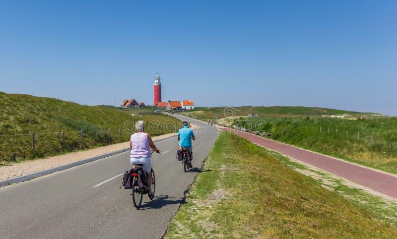 Couplez monter leurs bicyclettes au phare sur l'île de Texel images stock