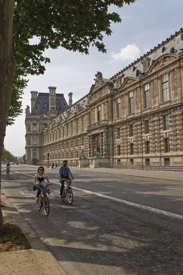 Couplez monter une bicyclette sur la rue de Paris photographie stock