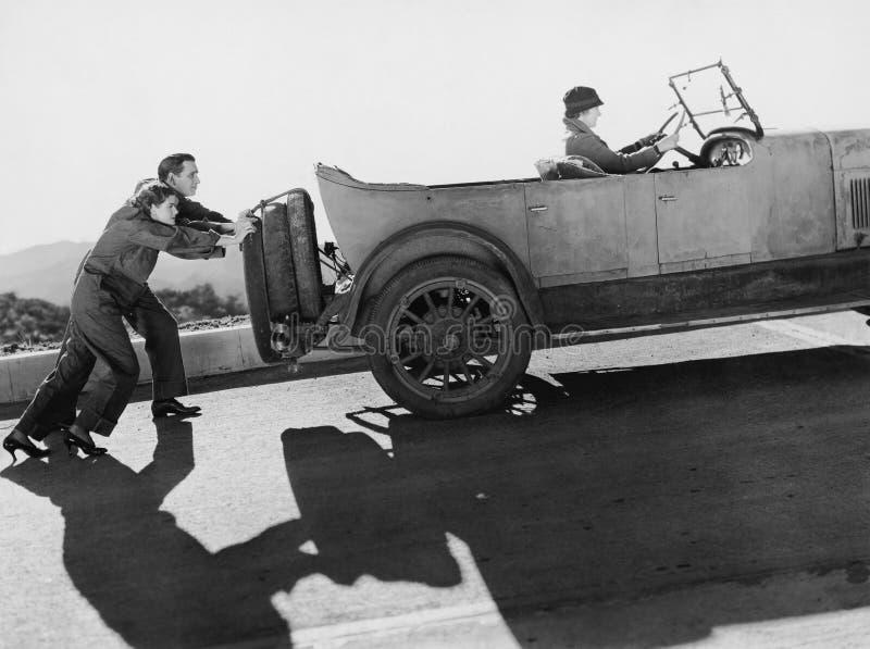 Couplez pousser la femme dans la voiture vers le haut de la colline (toutes les personnes représentées ne sont pas plus long viva photographie stock