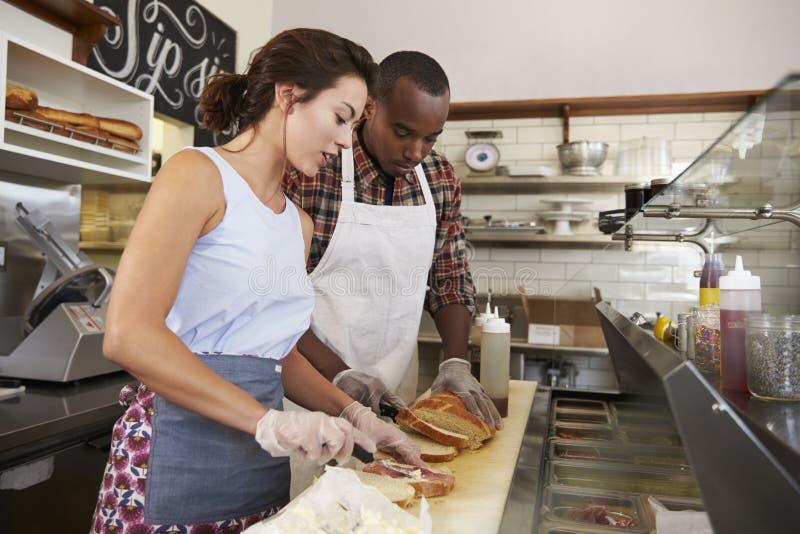 Couplez préparer des sandwichs à un compteur de barre de sandwich photographie stock libre de droits
