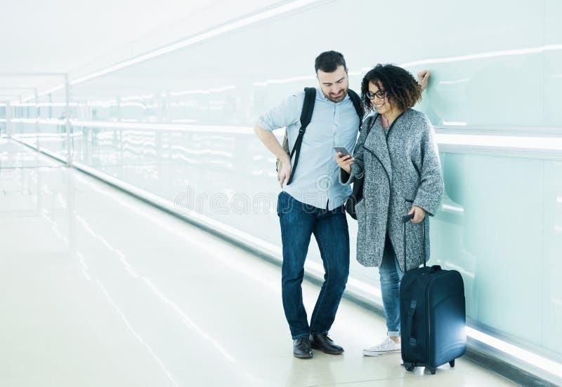 Couplez prêt à partir en vacances utilisant le voyage APP photos stock