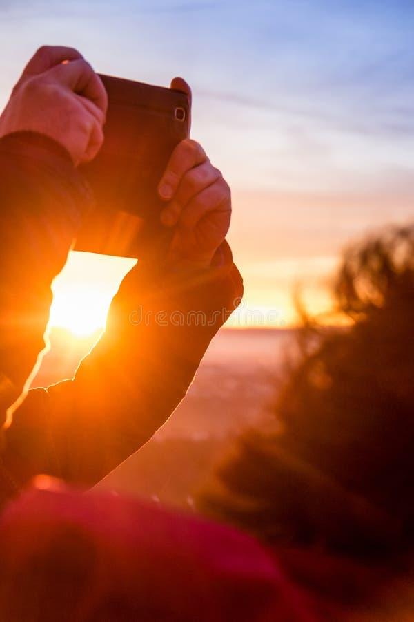 Couplez prendre des photos sur la plage au coucher du soleil images libres de droits