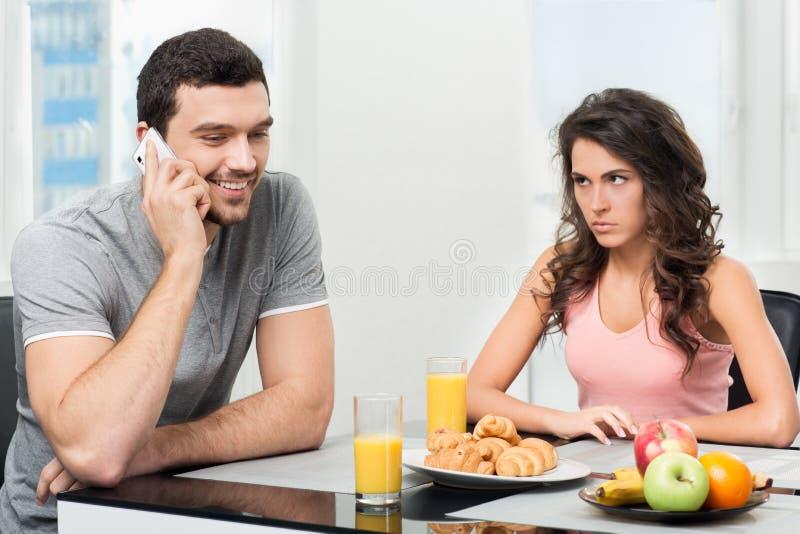 Couplez prendre le petit déjeuner, type parlant au téléphone image stock