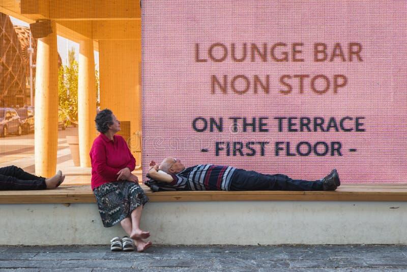Couplez prendre un repos à l'expo 2015 à Milan, Italie images libres de droits