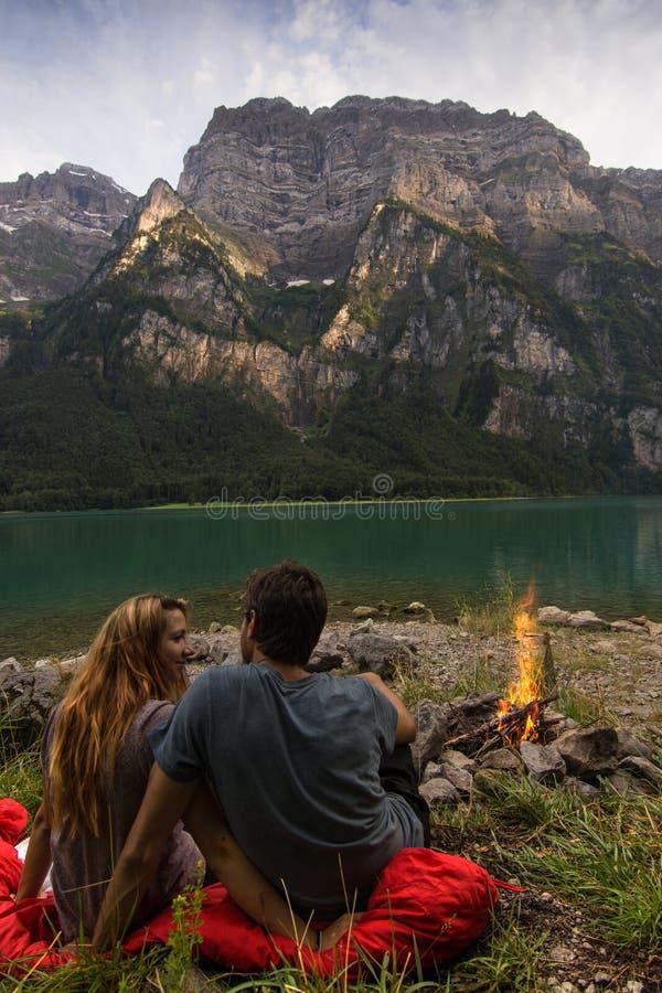 Couplez regarder l'un l'autre et la détente dans l'avant d'un beau lac de Suisse avec le feu à coté images libres de droits