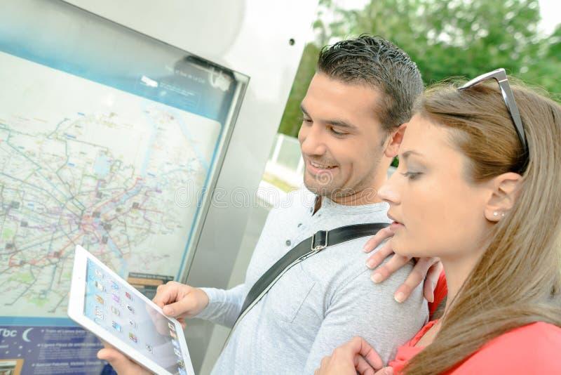 Couplez regarder le comprimé tenu dans la carte avant de ville photographie stock libre de droits