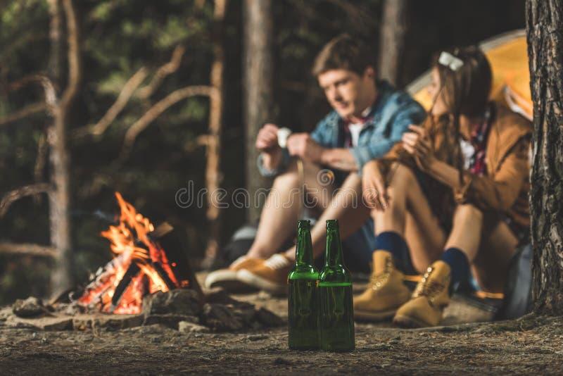 couplez se reposer à côté d'augmenter la tente avec deux bouteilles de bière images libres de droits