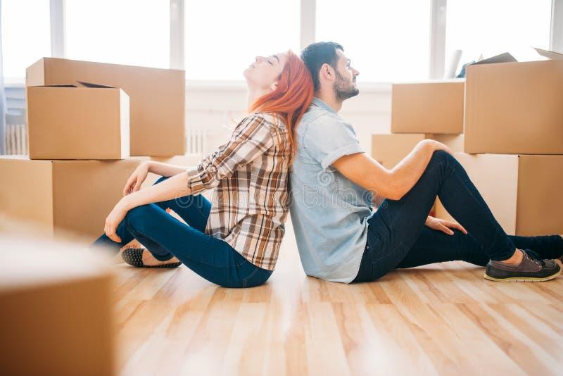 Couplez se reposer avec des dos entre eux, nouvelle maison image libre de droits