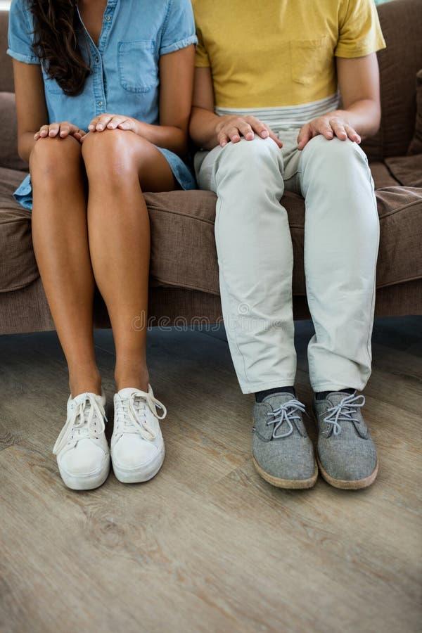 Couplez se reposer avec des mains sur des cuisses dans le salon photo stock