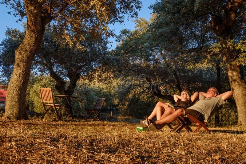 Couplez se reposer dans les chaises et appréciez le sunet photographie stock
