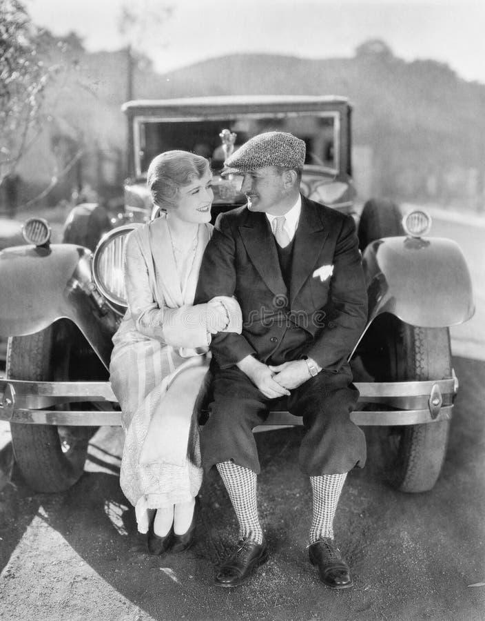 Couplez se reposer ensemble sur un pare-chocs de voiture (toutes les personnes représentées ne sont pas plus long vivantes et auc images libres de droits