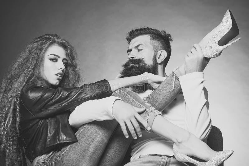Couplez se reposer sur la jeune femme de chaises utilisant les talons hauts noirs de diamante de jeans de veste en cuir tirant la images stock