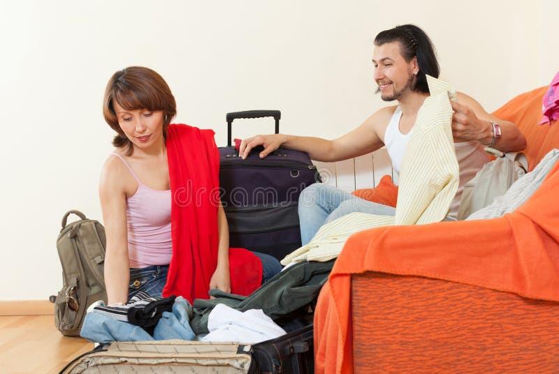 Couplez se reposer sur le divan et les paquets oranges une valise à la maison images libres de droits