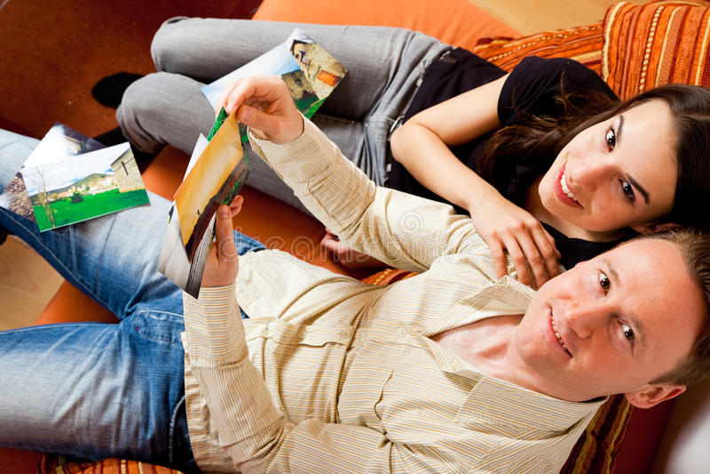 Couplez se reposer sur le divan regardant des photos photographie stock