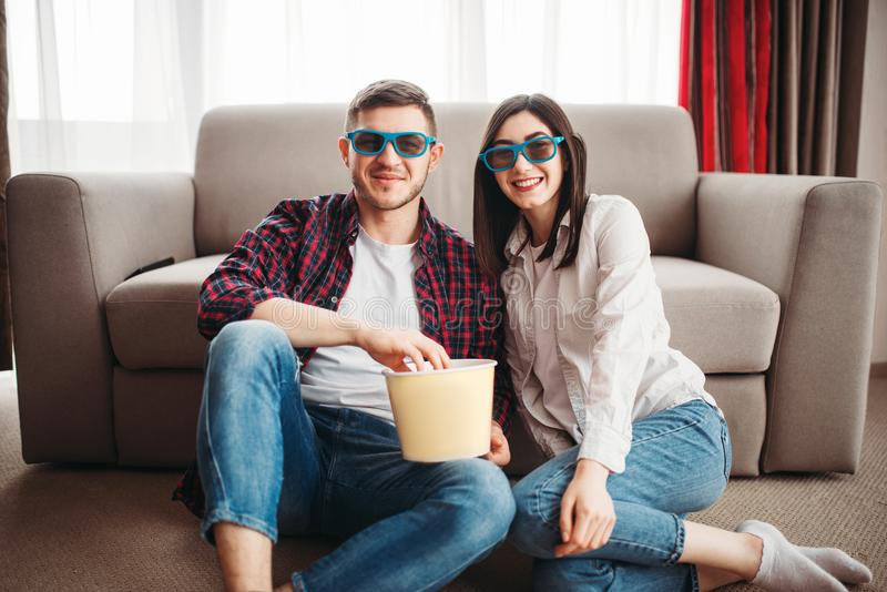 Couplez se reposer sur le plancher et regardez la TV avec le maïs éclaté image stock