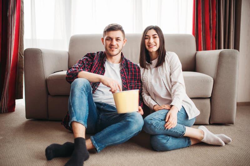 Couplez se reposer sur le plancher et regardez la TV avec le maïs éclaté photographie stock