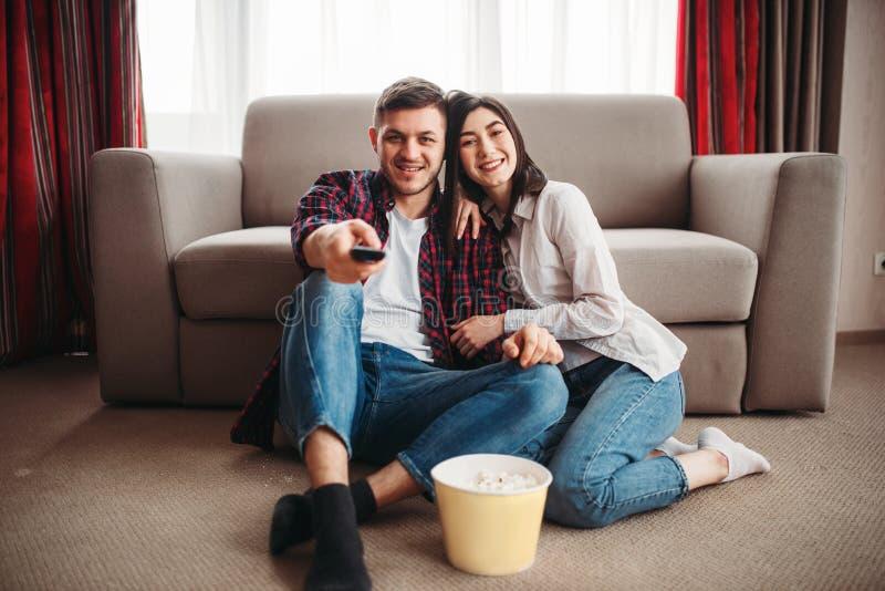Couplez se reposer sur le plancher et regardez la TV avec le maïs éclaté photo stock