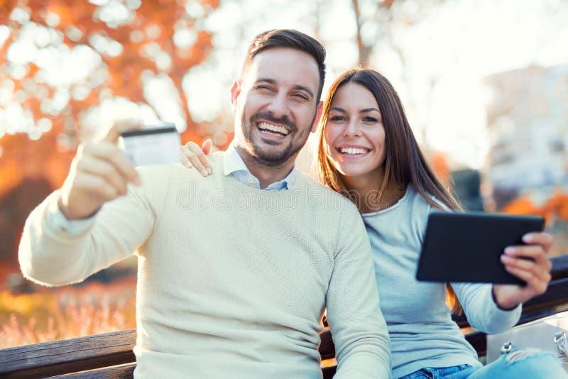 Couplez se reposer sur un banc et des utilisations de parc un comprimé numérique image libre de droits