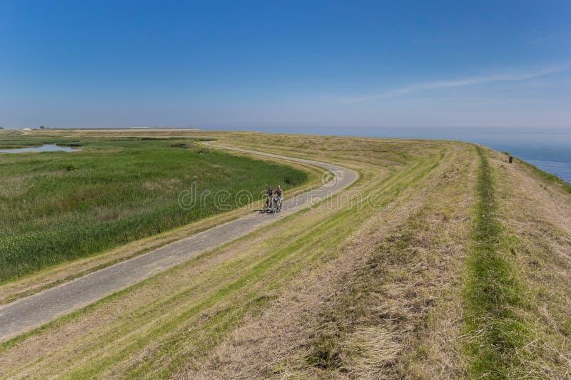 Couplez sur des bicyclettes le long d'une digue sur l'île de Texel images stock