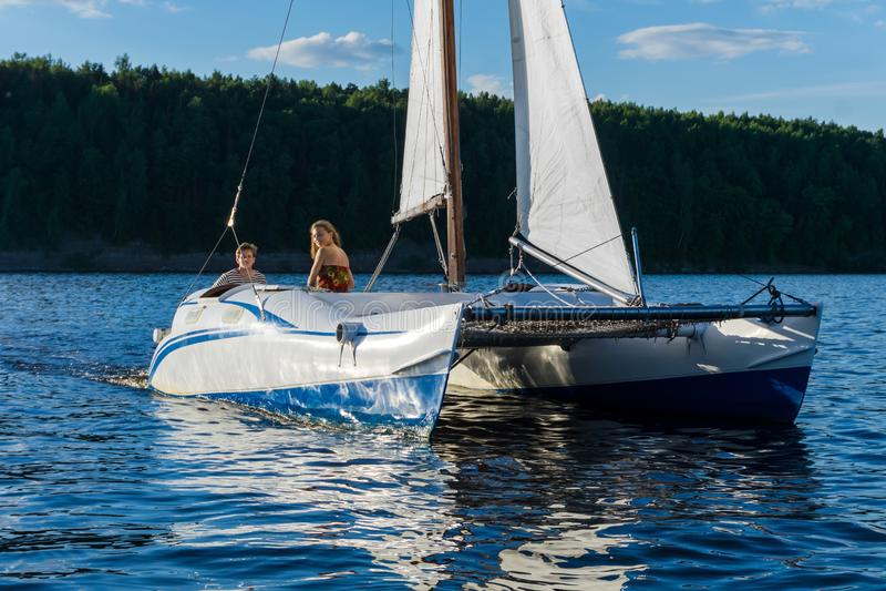 Couplez sur le bateau à voile de catamaran sur le fond du rivage photographie stock