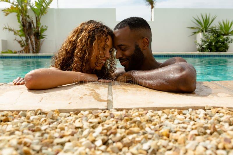 Couplez tête à tête au bord d'une piscine un jour ensoleillé photographie stock libre de droits