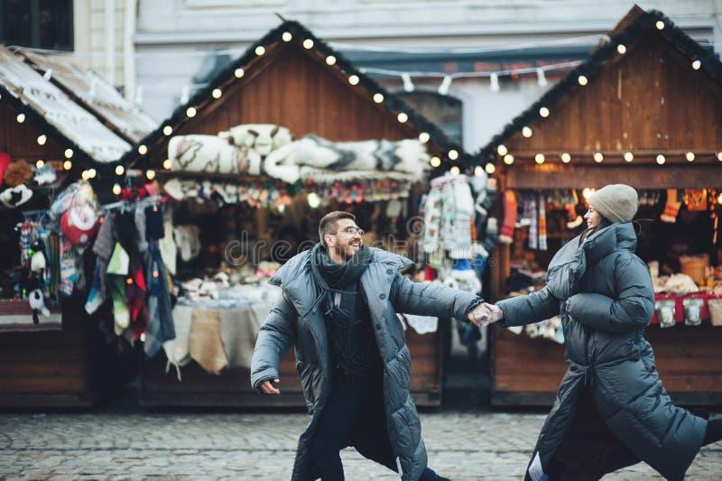 Couplez tenir des mains marchant sur le marché de Noël de ville regardant les FO photos libres de droits