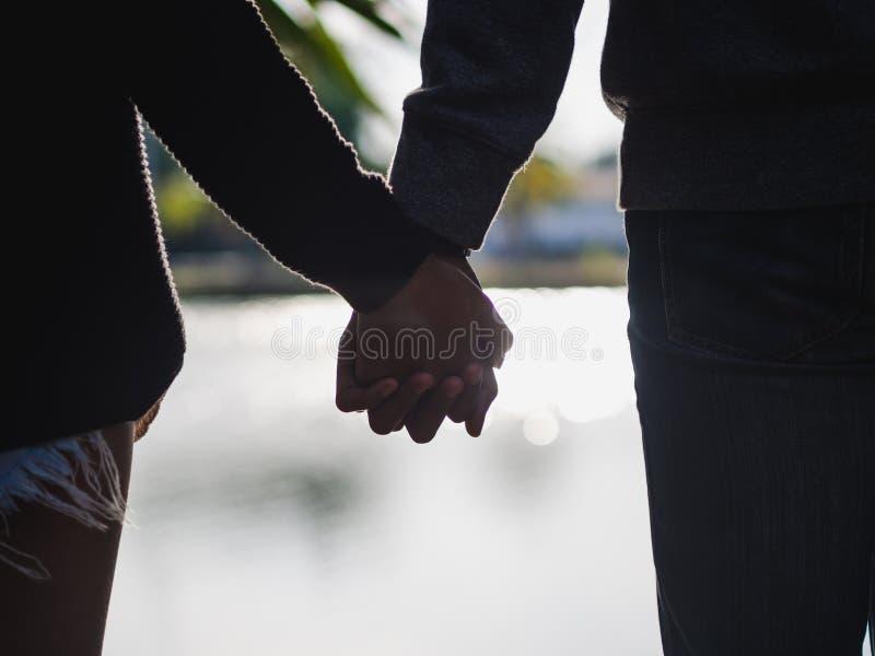 Couplez tenir des mains près du fond brouillé par lac Aimez et allez ensemble concept image stock