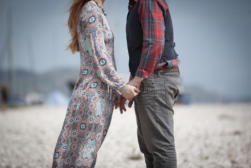 Couplez tenir des mains se faisant face sur une plage pendant l'été photo libre de droits