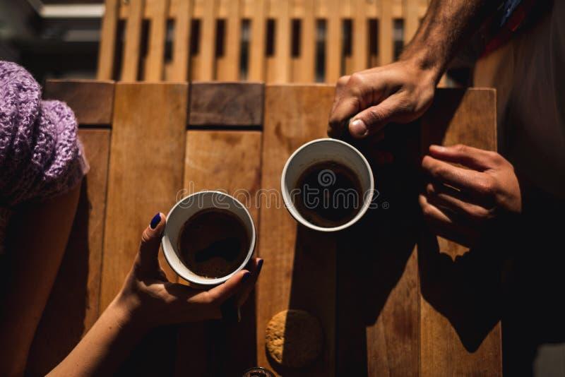 Couplez tenir des tasses de café sur la table image stock