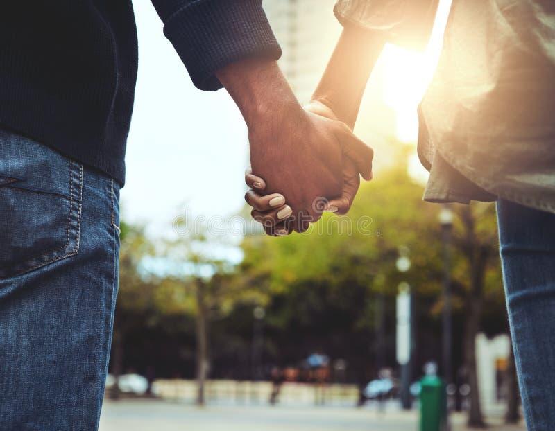 Couplez tenir les mains ensemble à l'extérieur photographie stock