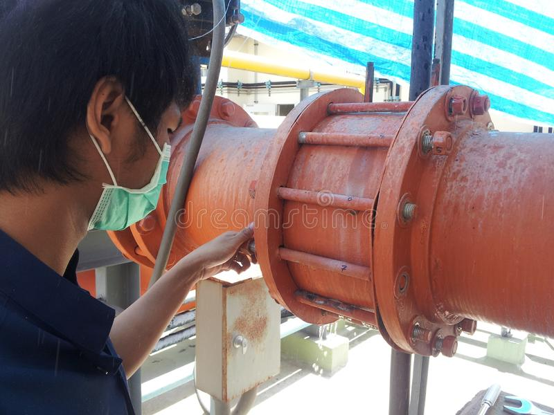 Coupling flange. The worker tightens the bolts on the Rubber Expansion Joint with hand for Cooling Tower. Technicians are removing the flange nut for pipe work stock photo